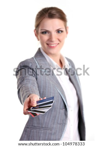 Young business woman smiling brightly and stretching out hand with plastic cards. Image with shallow depth of field, hand in focus.