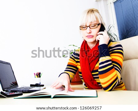 Young business woman speaking on mobile phone while using laptop at office