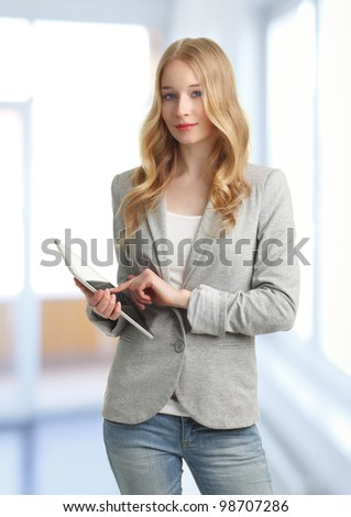 Young business woman standing in the office and holding a digital touch screen tablet in her hand