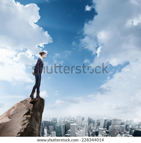 Young business woman standing on edge of rock mountain and looking at the city