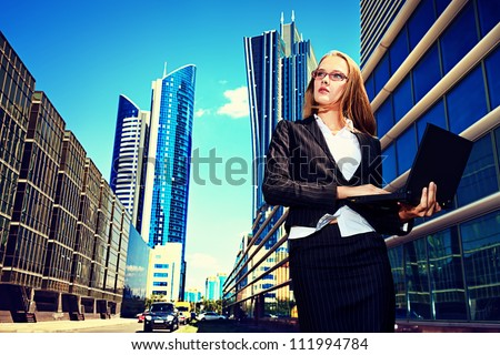 Young business woman standing with laptop in the big city and purposefully looking away. - stock photo