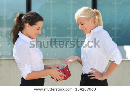 young business woman taking euro banknotes out from wallet and giving them to other woman - stock photo