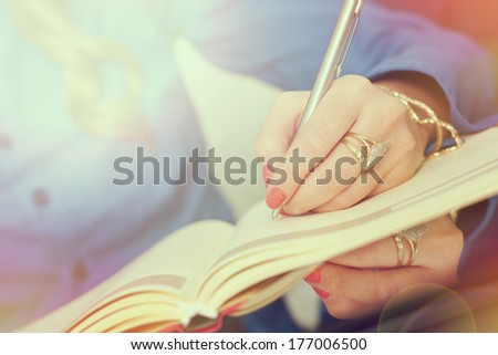 Young business woman taking notes on a meeting