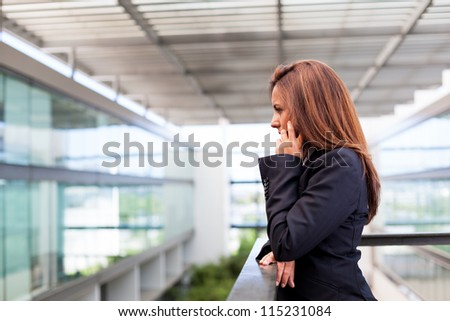 Young business woman talking on cell phone at the office - stock photo