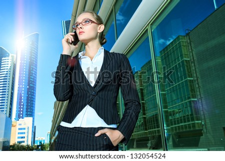 Young business woman talking on her mobile phone in the big city. - stock photo