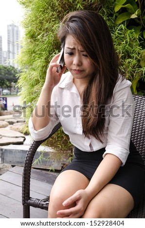 Young business woman talking on her mobile phone outdoor, tree background. - stock photo