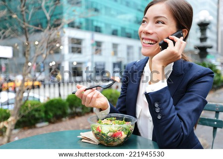 Young business woman talking on smartphone eating salad on lunch break in City Park living healthy lifestyle working on smart phone. Happy businesswoman, Bryant Park, manhattan, New York City, USA - stock photo