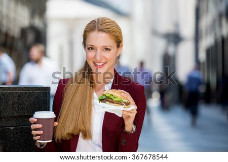 Young business woman talking on smartphone eating salad on lunch break in City Park living healthy lifestyle working on smart phone. Happy businesswoman