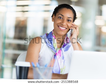 Young business woman talking over phone in front of her laptop
