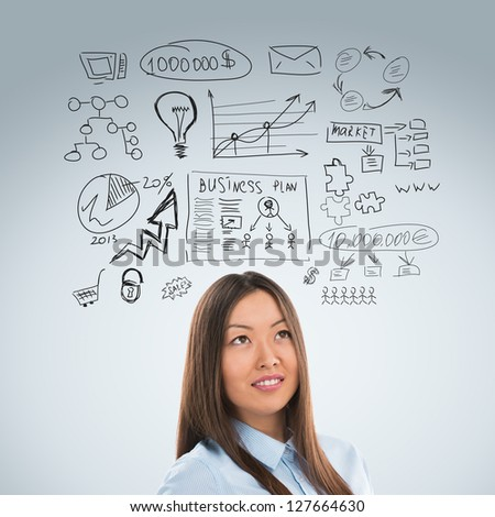Young business woman thinking of her plans closeup portrait and sketches overhead - stock photo