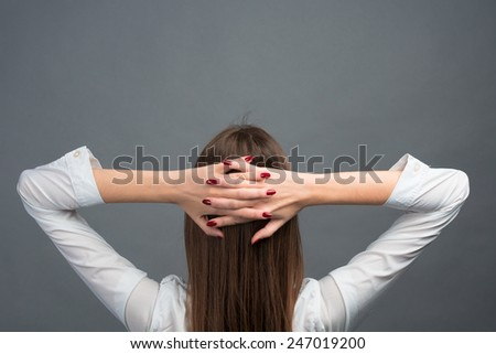 Young business woman thinking of her plans. space for text. gray background - stock photo