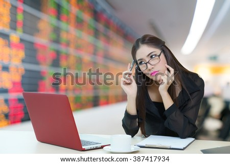Young business woman thinking with stock board on background - stock photo