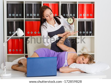 Young business woman tries to wake the sleeping coworker on a workplace in the office. Overworked. - stock photo