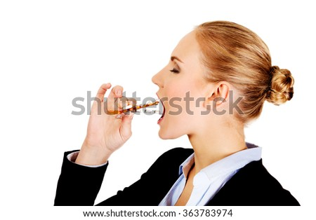 Young business woman trying to eat blister of pills - stock photo
