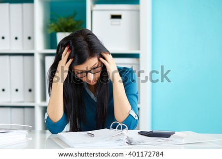 Young business woman under stress with head in hands - stock photo