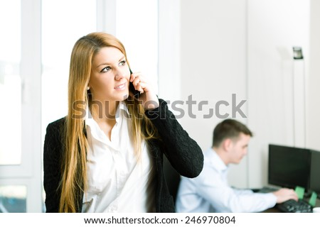 Young business woman using a mobile phone at office - stock photo