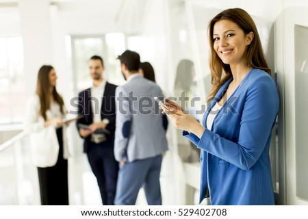 Young business woman using a mobile phone while business people talking in the background