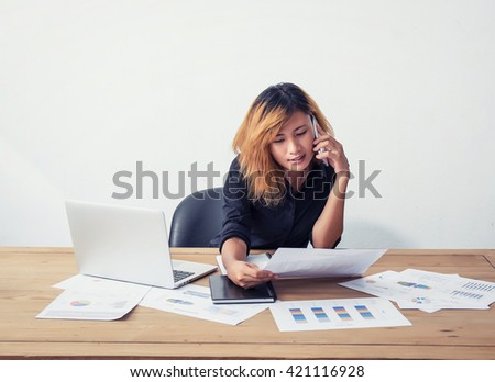 Young business woman using phone and work on workplace in office.
