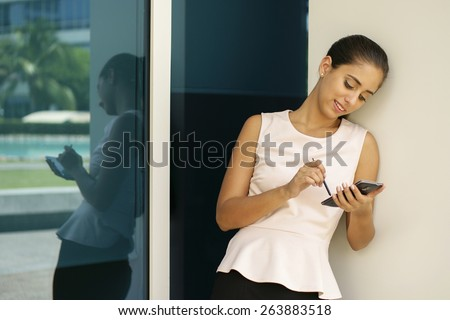 Young business woman using smartphone and taking notes on display with digital pen. The girl is outside office, leaning on a wall of building with reflections on window - stock photo