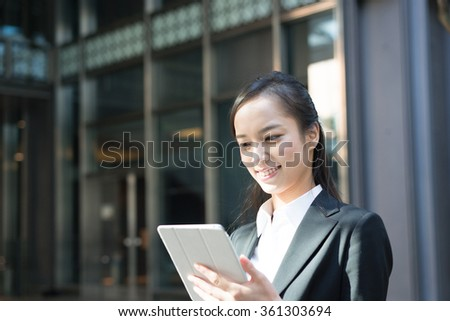 Young business woman using tablet computer - stock photo