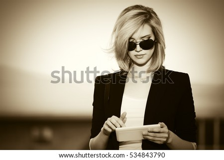Young business woman using tablet computer on city street Stylish fashion model in sunglasses outdoor