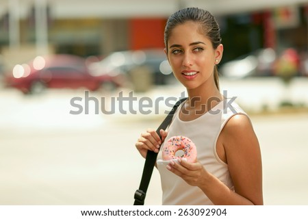 Young business woman walking to job doing breakfast eating pink donut from fast food on street. Front view, copy space - stock photo