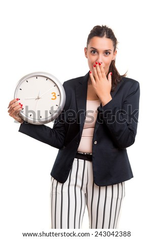 Young business woman, who seems to be late, looking at the clock - stock photo