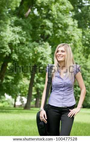 Young business woman wit laptob bag walking outdoors in park - stock photo