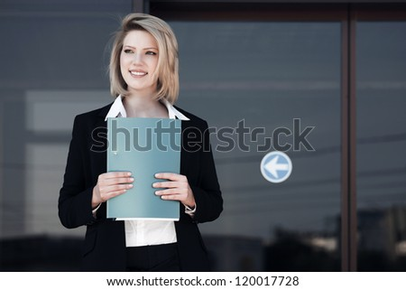 Young business woman with a folder against office windows - stock photo