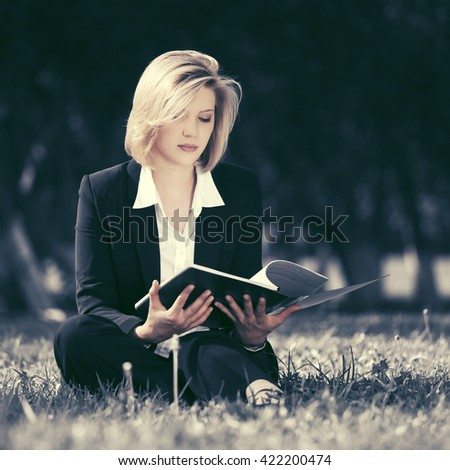 Young business woman with a folder on nature - stock photo