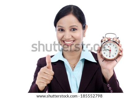 Young business woman with an alarm clock against white background - stock photo
