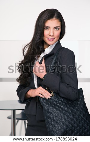 Young business woman with bag over her shoulder on a break at work - stock photo