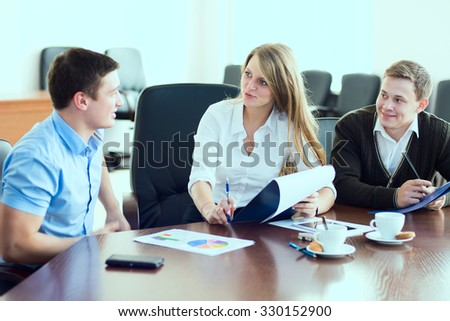 Young business woman with business partners, men at a business meeting. A group of businessmen on the signing of the contract - stock photo