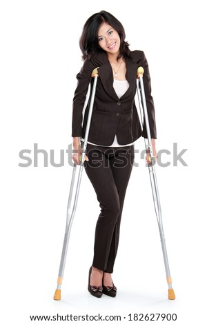 Young business woman with crutches, isolated on white background - stock photo