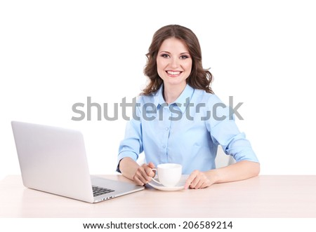 Young business woman with cup sitting at table with notebook in room
