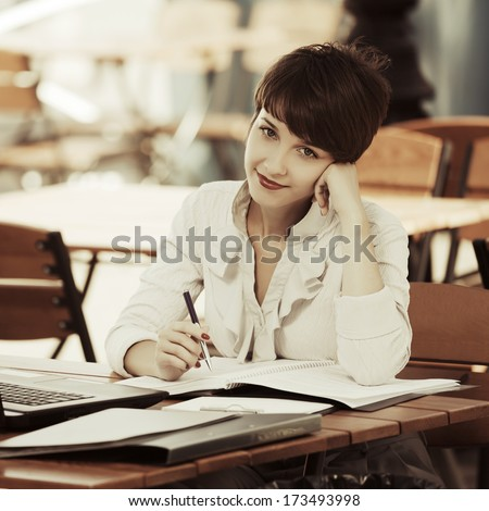 Young business woman with financial papers at sidewalk cafe