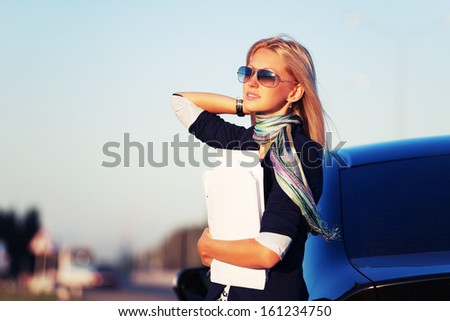 Young business woman with financial papers at the car - stock photo