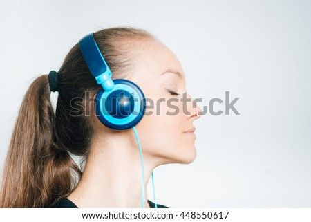 young business woman with headphones dancing to the music, isolated on a gray background