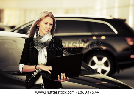 Young business woman with laptop on the car parking  - stock photo