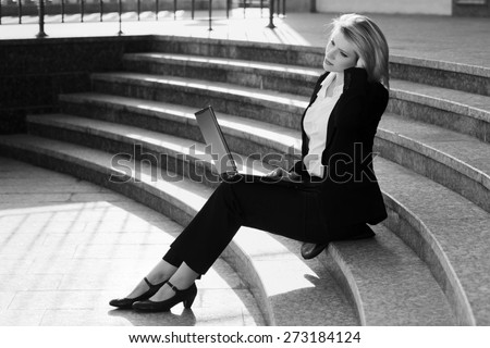 Young business woman with laptop on the steps - stock photo