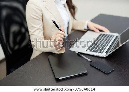 Young business woman with notebook in the office - stock photo
