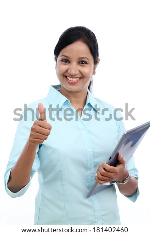 Young business woman with tablet and making thumbs up gesture against white - stock photo