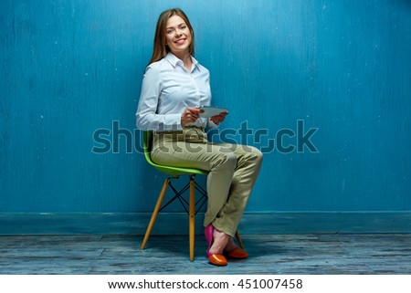Young business woman with tablet sitting on chair. White shirt. Blue wall. - stock photo