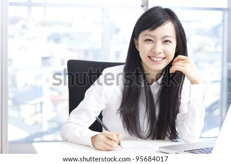 Young business woman working at office - stock photo
