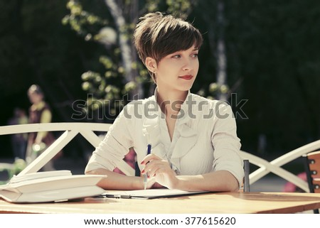 Young business woman working at sidewalk cafe  - stock photo