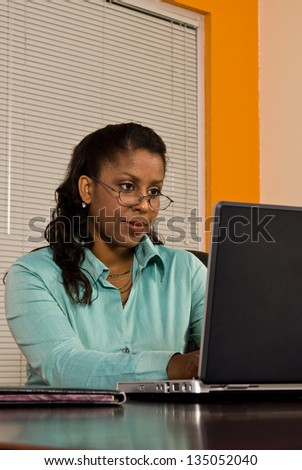 Young business woman working on a laptop computer - stock photo