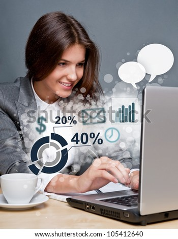Young business woman working on her laptop. Different icons with functional symbols are flying out of the screen - stock photo