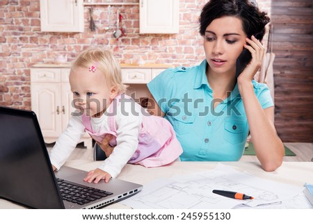 Young business woman working with baby in the kitchen