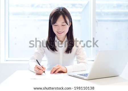 Young business woman working with laptop computer at the office - stock photo