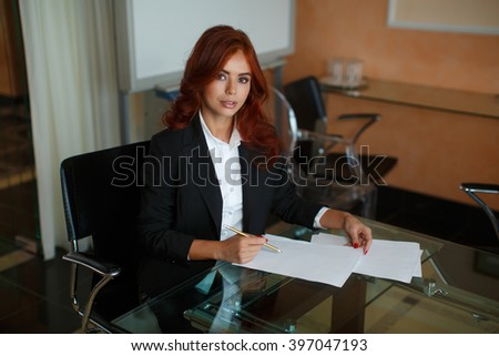 young business woman working with papers sitting at the table